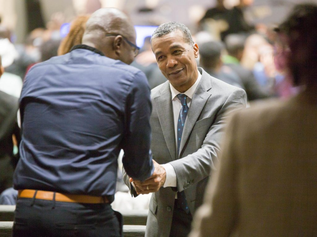 Welcome TO APC: Pastor Audley Castro Shaking A Male Guests Hands and Smiling